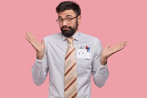 Onwetende mannelijke professor verbaasd aarzelend blik spreidt zijn handpalmen van verontwaardiging, draagt formeel overhemd, stropdas en bril, heeft donkere stoppels Gratis Foto