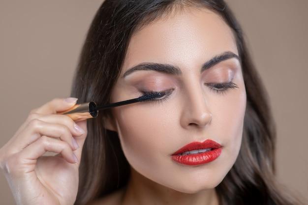 Oog cosmetica. gezicht van ernstige betrokken mooie vrouw met hangende oogleden met borstel met mascara in de buurt van haar oog Premium Foto