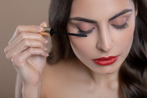 Oog make-up. jonge mooie donkerharige vrouw bezig met het toepassen van mascara op oogleden aandachtig met de oogleden naar beneden Premium Foto