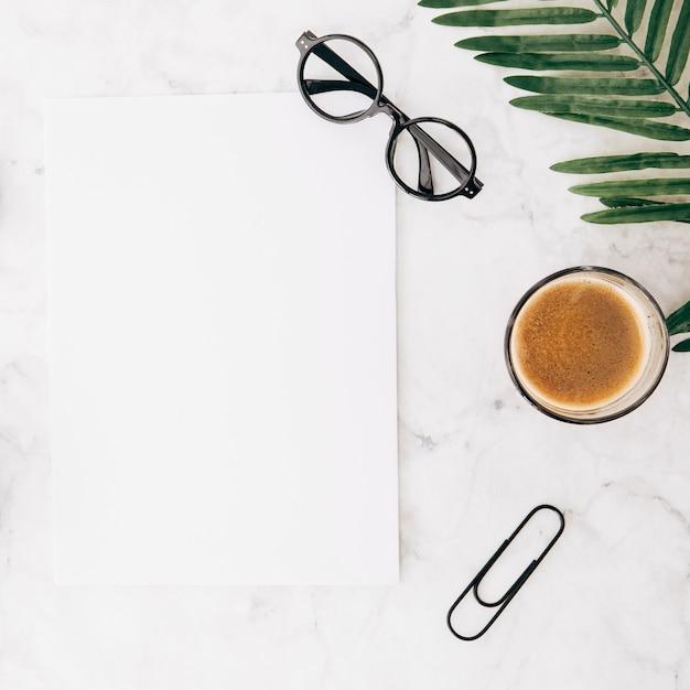 Oogglazen op leeg witboek met koffieglas; paperclip en bladeren op gestructureerde achtergrond Gratis Foto