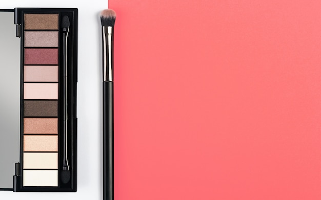 Oogschaduw en penseel op wit en koraal kleur achtergrond Premium Foto