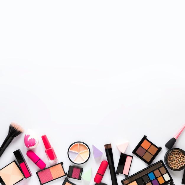 Oogschaduw met lippenstift en poederborstel op tafel Gratis Foto