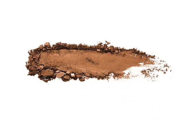 Oogschaduw monster geïsoleerd. gemalen bruine metalen oogschaduw. het concept van mode- en schoonheidsindustrie. Premium Foto