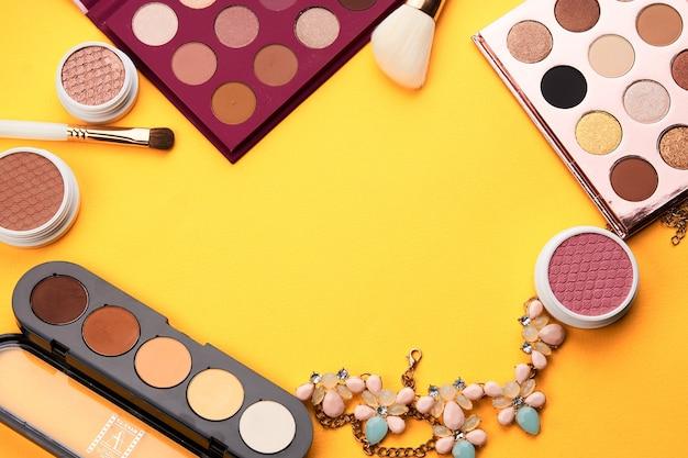 Oogschaduw professionele cosmetica blozen poeder gele achtergrond bovenaanzicht. Premium Foto