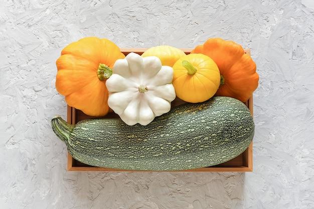 Oogst gekleurde verschillende groenten kalebassen pompoen, courgette, pompoen in een houten doos Premium Foto