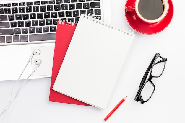 Oortelefoons en spiraalvormige blocnotes op laptop met koffiekop en oogglazen Gratis Foto
