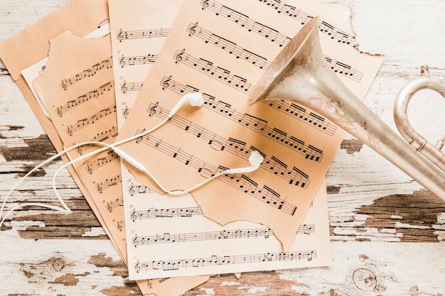 Oortelefoons en trompet op bladmuziek Gratis Foto