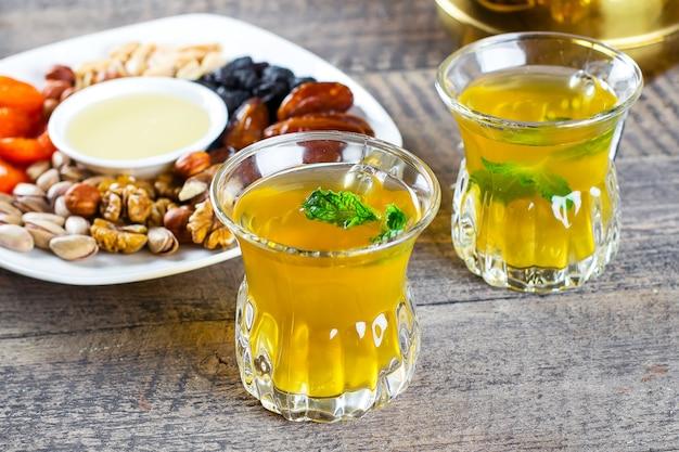 Oosterse thee met munt, honing, noten en gedroogde vruchten op houten tafel. ramadan drankje Premium Foto