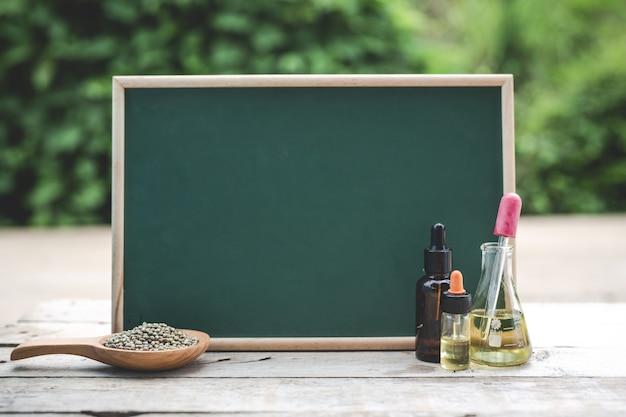 Op de houten vloer is er hennepolie, hennepzaden. en het groene bord is leeg om tekst te plaatsen. Gratis Foto