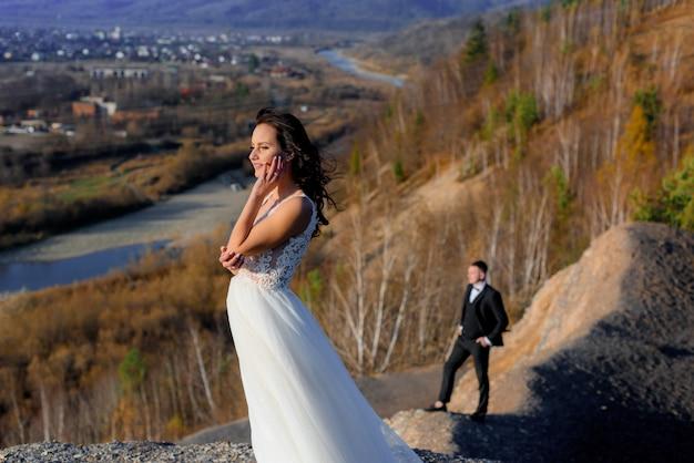 Op de zonnige herfstdag op de heuvel staat bruid op de voorgrond en een wazige bruidegom op de achtergrond Gratis Foto