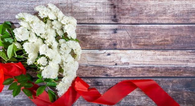 Op donkere planken ligt een boeket witte rozen met een rood lint. Premium Foto