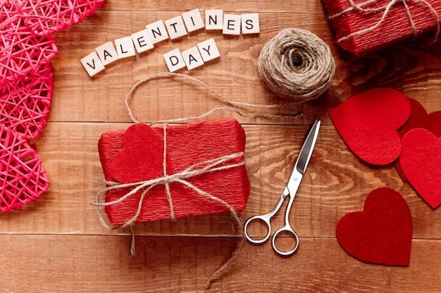 Op een houten tafel ligt een handgemaakt geschenk verpakt in golfpapier. valentijnsdag Premium Foto