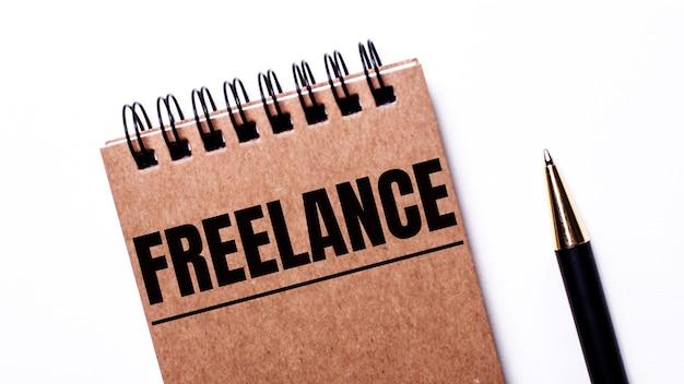 Op een lichte muur, een zwarte pen en een bruin notitieboekje op zwarte veren met het opschrift freelance Premium Foto