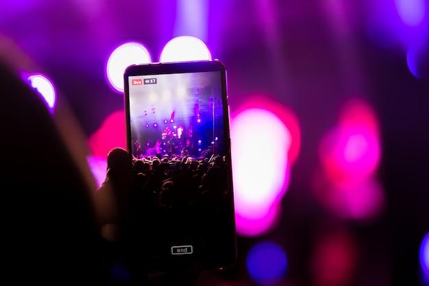 Op een muziekfestival maakt hij live video op een fansmartphone Premium Foto