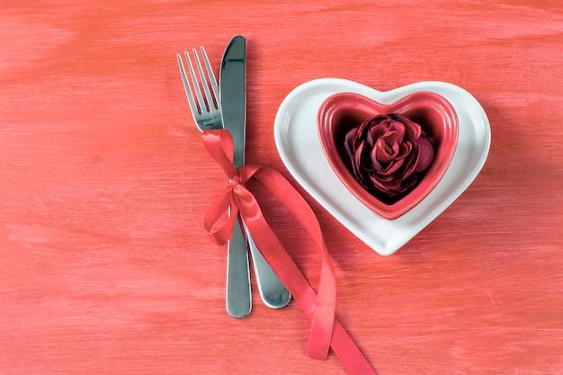 Op een rode tafel staan twee hartvormige borden, een rode rozeknop en bestek vastgebonden met een rood lint Premium Foto