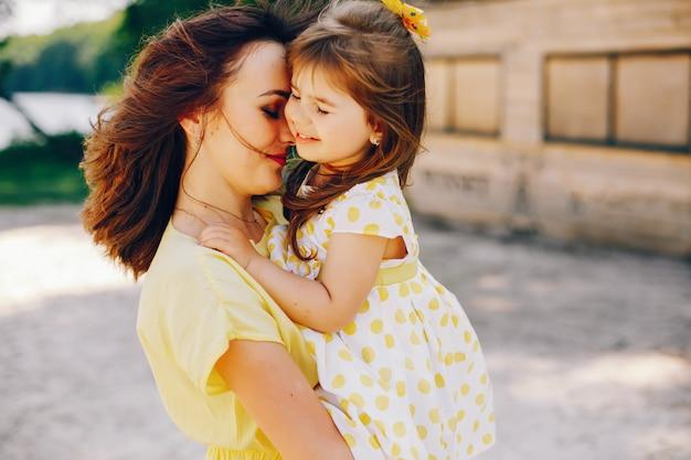 Op een zonnig strand met geel zand loopt mama in een gele jurk en haar kleine mooie meisje Gratis Foto