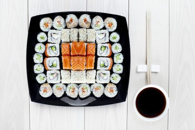Op een zwart vierkant bord wordt een grote sushi-set neergelegd. bovenaanzicht. lichte houten tafel. ernaast staat een kom sojasaus en een eetstokje. heerlijke lunch of diner in japanse stijl. zachte focus. Premium Foto