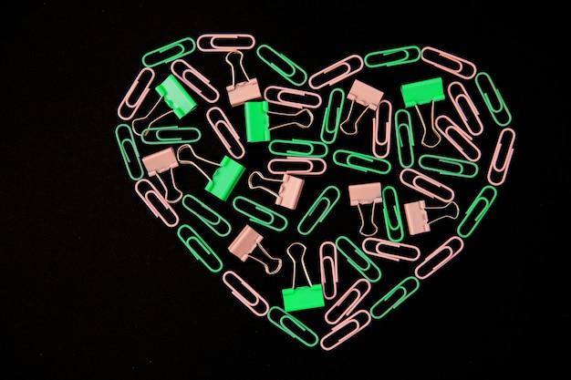 Op een zwarte achtergrond zijn de hartvormige paperclips groen en roze. kantoor artikelen. achtergrond en textuur. het concept van valentijnsdag. Premium Foto