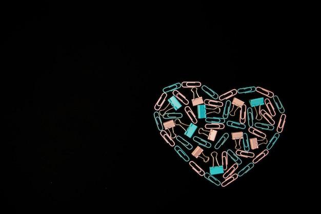 Op een zwarte achtergrond zijn paperclips in de vorm van een hart blauw en roze. kantoor artikelen. achtergrond en textuur. het concept van valentijnsdag. Premium Foto