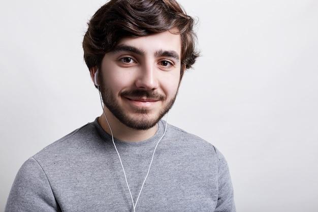 Op het ritme van muziek. een close-up van stijlvolle hipster met baard grote bruine ogen en modern kapsel in oortelefoons met een aangename glimlach Premium Foto