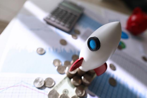 Op kleurenkaart is speelgoed ruimteraket en munten liggen op tafel Premium Foto