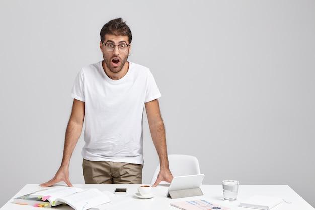 Op nee. portret van aantrekkelijke bug eyed bebaarde donkerharige mannelijke werknemer permanent aan zijn bureau Gratis Foto