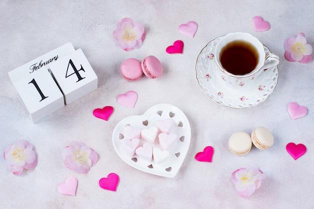 Op tafel staat een kopje thee, roze bloemen, hartvormige marshmallows, satijnen harten, bitterkoekjes en een kalenderdatum van 14 februari Premium Foto