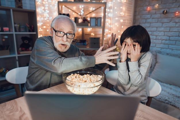 Opa-kleinzoon kijken naar enge film op laptop Premium Foto
