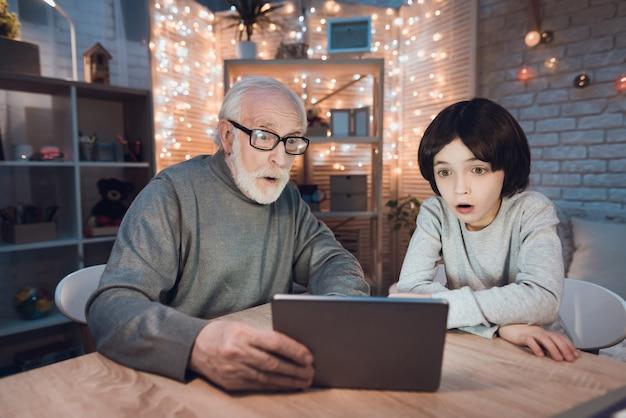 Opa-kleinzoon kijken naar enge film op tablet Premium Foto