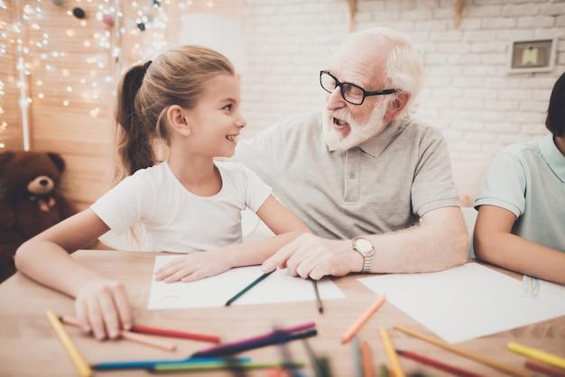 Opa met grijs haar leert gelukkig meisje tekenen. Premium Foto