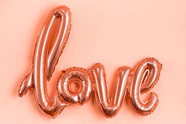Opblaasbare letters liefde in koraalkleur op roze koraal plat lag Premium Foto