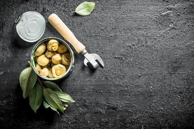 Open blik met champignons uit blik. op zwarte rustieke achtergrond Premium Foto