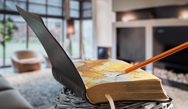 Open boek bijbel met potlood, op de achtergrond van de woonkamer. een boek lezen in een gezellige omgeving. Gratis Foto