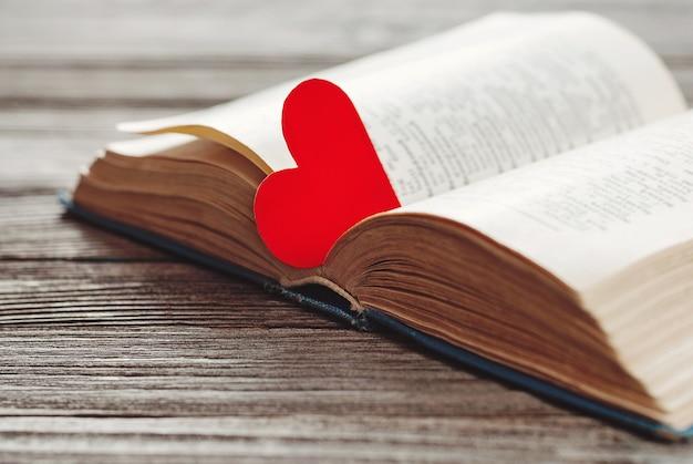 Open boek met rode hartvormige papieren bladwijzer op houten tafel Premium Foto