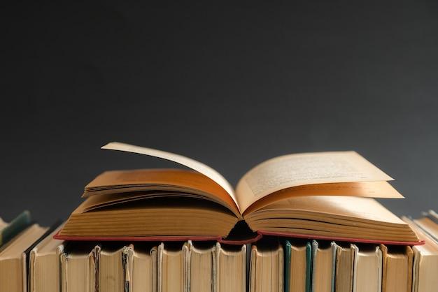 Open boek op zwarte achtergrond, hardback boeken op houten tafel. onderwijs en leren. Premium Foto