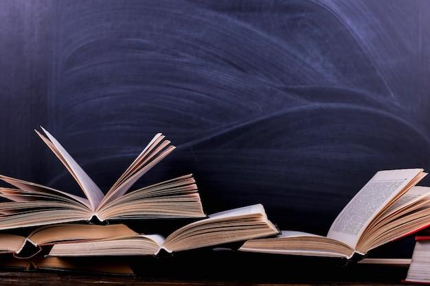 Open boeken zijn een stapel op het bureau, tegen de achtergrond van een schoolbord Premium Foto