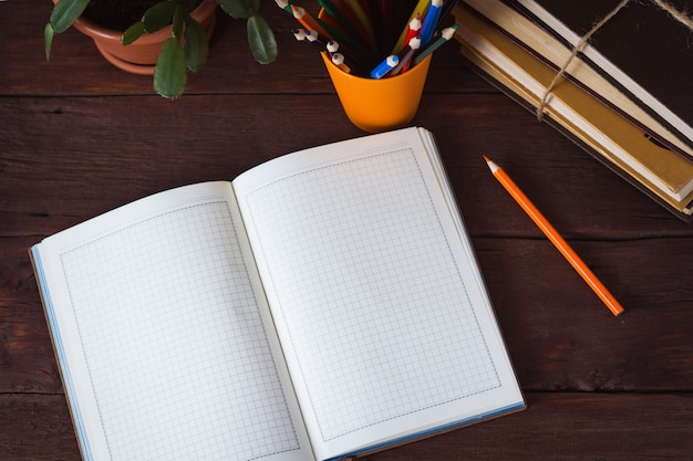 Open dagboek, kleurpotloden in een glas, stapel boeken, kamerbloem op een houten oppervlak Premium Foto