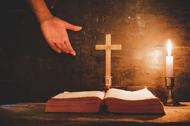 Open de bijbel en kaars op een oude eikenhouten tafel. Gratis Foto