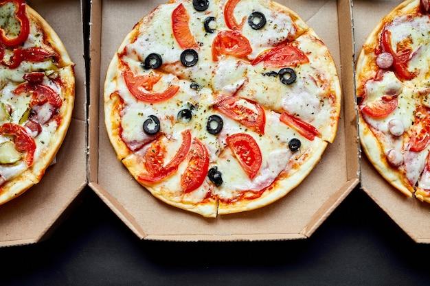 Open dozen met hete smakelijke italiaanse gesneden drie pizza's op zwarte achtergrond Premium Foto