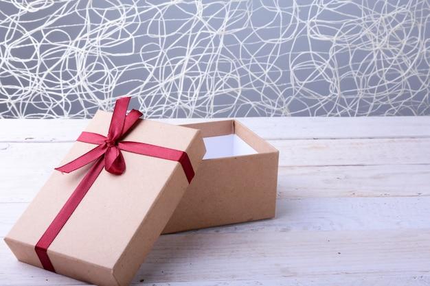 Open geschenkdozen met strik op hout achtergrond. kerst decoratie Premium Foto