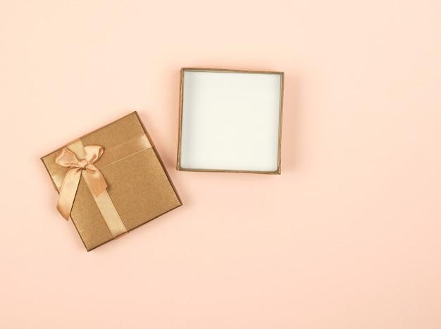 Open gouden vierkante geschenkdoos met een strik Premium Foto
