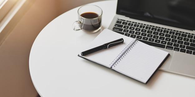 Open laptopcomputer met kantoorbenodigdheden op een comfortabele werkplek Premium Foto