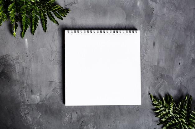 Open leeg spiraalvormig notitieboekje, grijze schoollevering op concrete achtergrond Premium Foto
