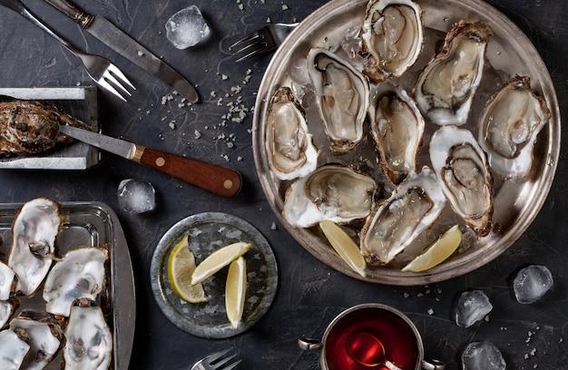 Open oesters op een bord met plakjes citroen en ijs. bovenaanzicht Premium Foto