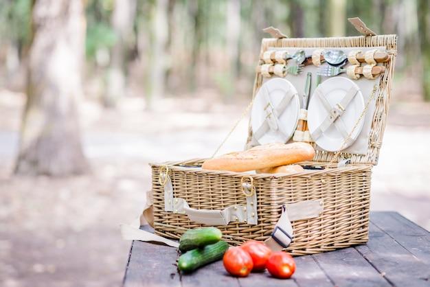 Open picknickmand met tomaten, komkommers en brood over een houten tafel in het park. Premium Foto