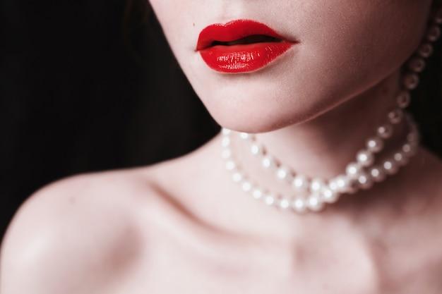 Open rode lippen en parels rond de nek op een zwarte achtergrond. elegante vrouwelijke portret in retro stijl. fetisj seksueel concept. mode portret van een jong meisje close-up. Premium Foto