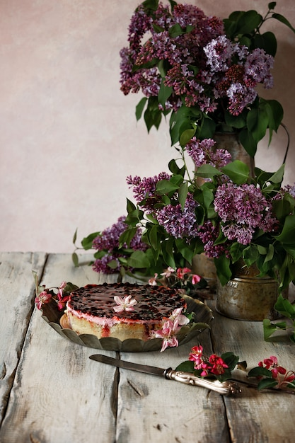 Open taart met bessengelei en bessen op een vintage schaaltje. stilleven met takken van lila Premium Foto