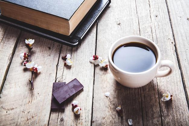 Open vintage boek met bloesem tak van kersenboom op houten tafel. een kop koffie Premium Foto