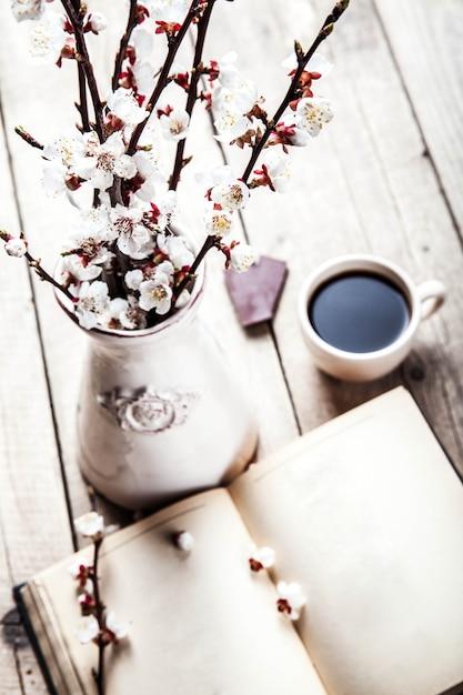 Open vintage boek met bloesemtak van kersenboom op houten tafel met een mooie vintage vaas en een kopje koffie Premium Foto