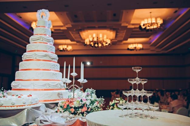 Open vlakteglazen met huwelijkscake en kroonluchter in huwelijksceremonie Premium Foto